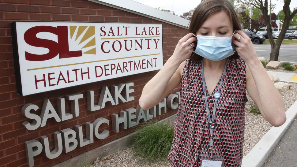 (Rick Bowmer | AP file photo) In this May 19, 2020, file photo, health investigator Mackenzie Bray adjusts her mask at the Salt Lake County Health Department, in Salt Lake City. Bray normally works to track contacts for people with sexually transmitted diseases, but she was reassigned during the coronavirus pandemic. She is now one of 130 people at this county health department assigned to track down COVID-19 cases in Utah's urban center around Salt Lake City. The investigators, many of them nurses, each juggle 30 to 40 cases that can include a total of several hundred people.