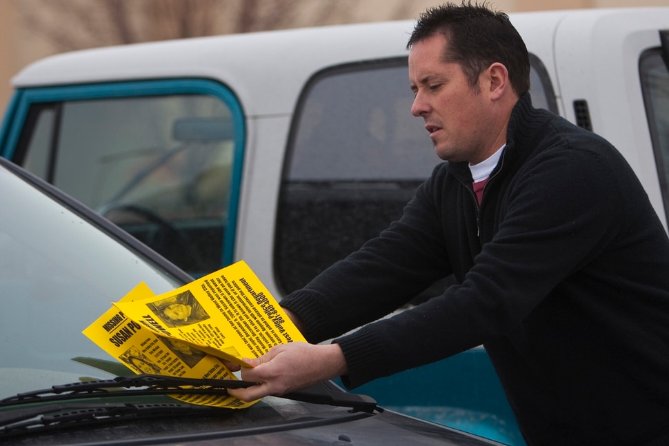 (Chris Detrick | Tribune file photo) Paul Timpson places missing-person fliers of Susan Powell on cars in a Smith's parking lot Saturday, Dec. 12, 2009.