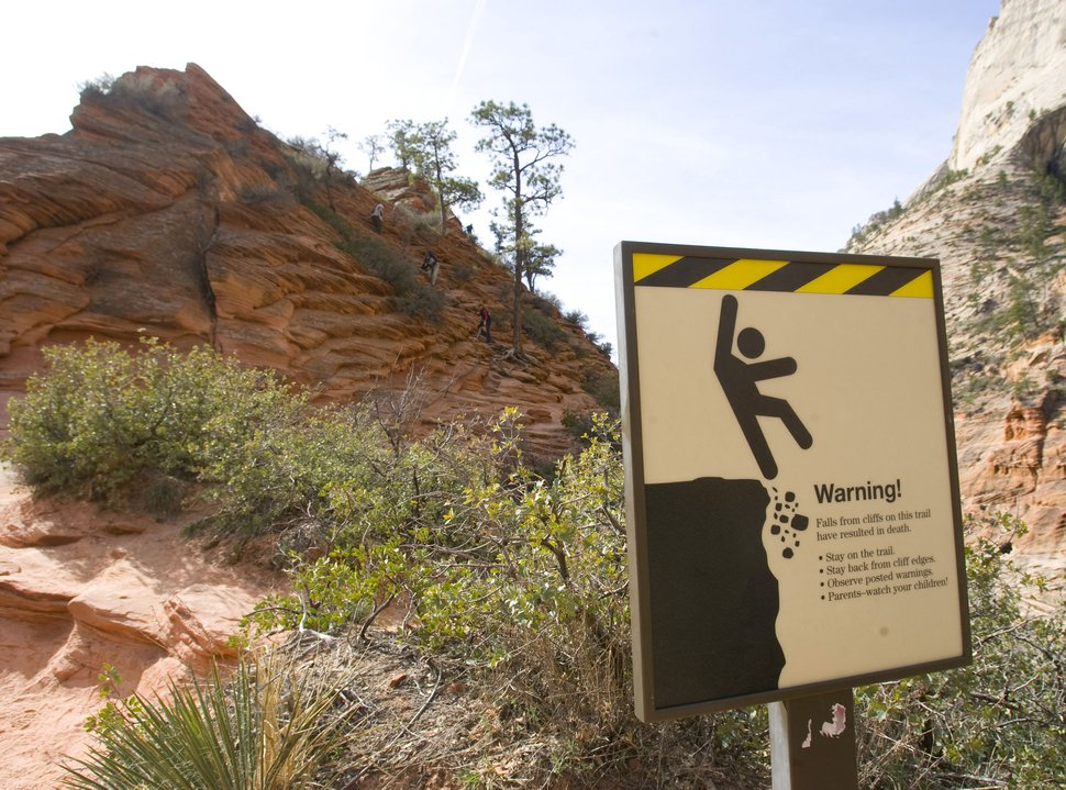 (Al Hartmann | Tribune file photo) Sign at the bottom of the Angel's Landing Trail warns hikers of the dangers of the hike ahead. It's a safe area named Scout's Lookout where hikers can decide whether to continue up the steep, exposed Angel's Landing hike or turn around.
