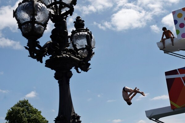 A diver performs off the Alexandre III bridge above the Seine river in Paris, Friday, June 23, 2017. Paris is aiming to boost its bid for the 2024 Olympics by turning some of its world-famous landmarks over to sports for two days, with 100-meter races on a track floating on the Seine, high-diving into the river, cycling around the Arc de Triomphe and other events to showcase the French capital's suitability for the games. (AP Photo/Thibault Camus)