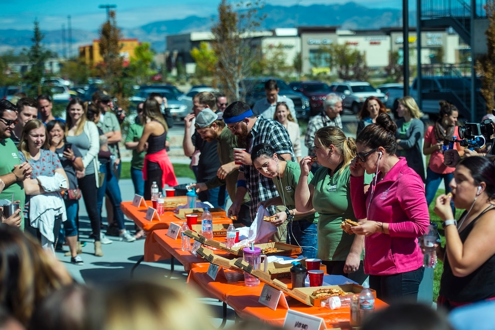 (Chris Detrick | The Salt Lake Tribune) Employees compete in a pizza eating competition during a fundraiser for United Way at CHG Healthcare Wednesday, September 20, 2017.