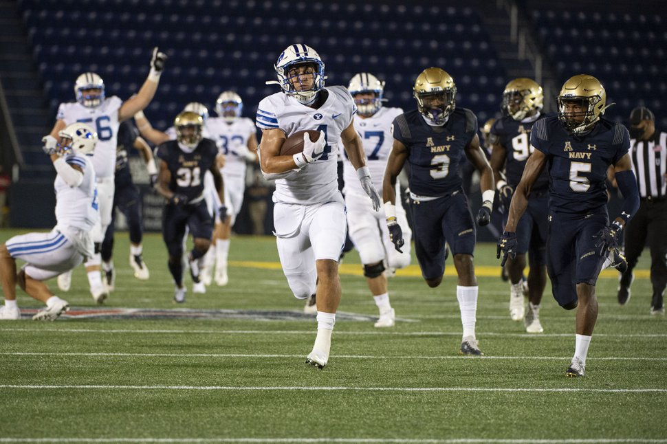 FILE - In this Monday, Sept. 7, 2020 file photo, BYU running back Lopini Katoa runs for a touchdown as Navy cornerback Michael McMorris (5) and defensive back Cameron Kinley (3) chases during the first half of an NCAA college football game in Annapolis, Md. (AP Photo/Tommy Gilligan, File)