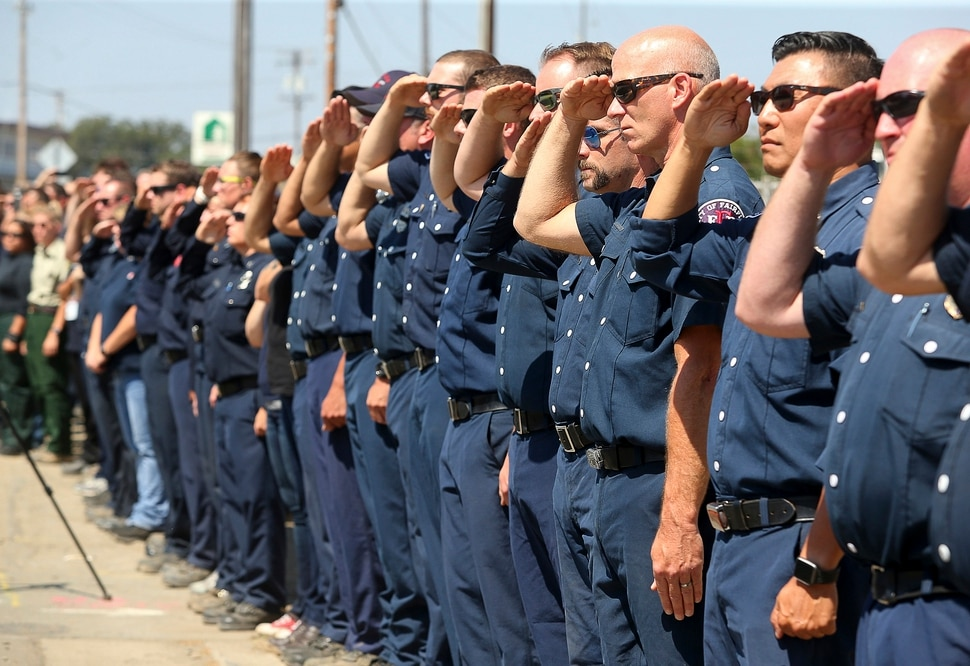 (Christopher Chung | The Press Democrat via AP) Firefighting personnel from various agencies salute as the procession for Battalion Chief Matthew Burchett travels along North State Street, in Ukiah, Calif., on Wednesday, Aug. 15, 2018. Burchett said goodbye to his wife and 7-year-old son in early August, volunteering to travel with fellow firefighters from Utah to help battle record-setting blazes in California. Burchett was hit by a falling tree and died Monday night while fighting the largest blaze in California history, the Mendocino Complex fire north of San Francisco.