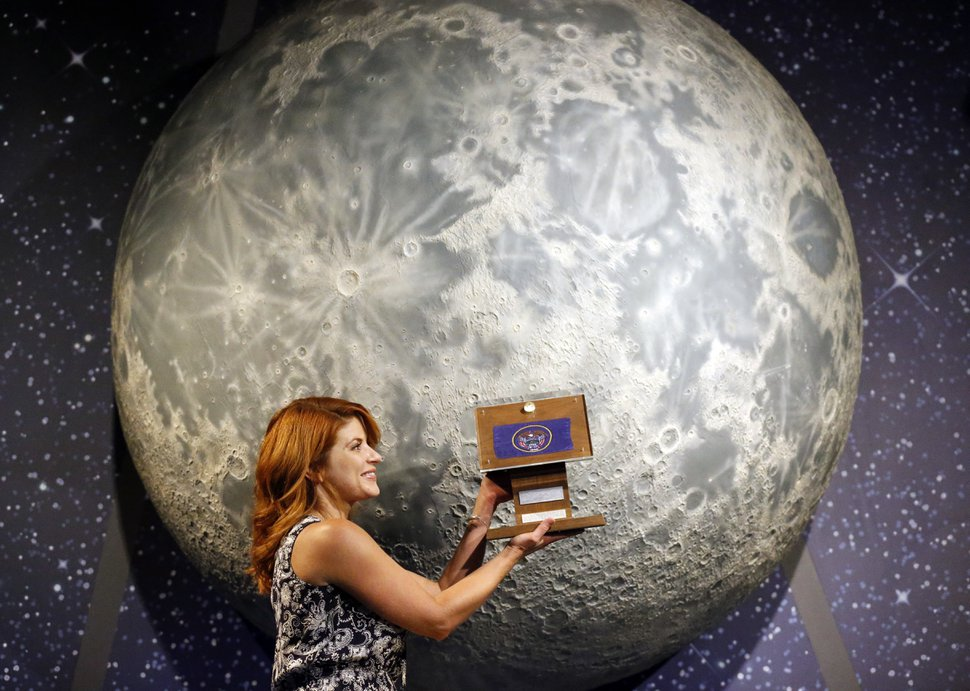 (Rick Bowmer | The Associated Press) In this Thursday, Aug. 23, 2018, photo, Lindsie Smith, from the Clark Planetarium, holds moon rocks encased in acrylic and mounted on a wooden plaque at the Clark Planetarium, in Salt Lake City. A former NASA investigator who has spent more than a decade tracking missing moon rocks is closing in on his goal of finding all 50 lunar samples gifted to U.S. states after Neil Armstrong's first steps on the moon. In recent weeks, two more of the moon rocks that dropped off the radar after the 1969 Apollo 11 mission have been located in Louisiana and Utah.
