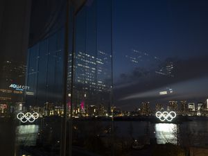 (Jae C. Hong   AP) The Olympic rings are reflected in the glass wall of a wedding chapel in the Odaiba section of Tokyo, Monday, March 23, 2020. The Tokyo Olympics are going to happen — but almost surely in 2021 rather than in four months as planned.