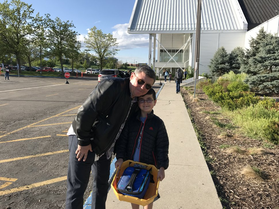 (Courtney Tanner | The Salt Lake Tribune) Ruslan Stepanenko and his son, Max, smile as they walk into the American International School of Utah on Thursday, May 9, 2019. The school will close after years of financial struggles.