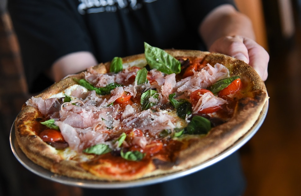 (Francisco Kjolseth | The Salt Lake Tribune) A customer gets a create your own pizza at Wicked Peel Pizza Kitchen in Riverton.