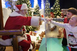 (AP Photo/Seth Wenig) Julianna, 3, and Dylan Lasczak, 5, visit with Santa through a transparent barrier at a Bass Pro Shop in Bridgeport, Conn., on Nov. 10, 2020. In this socially distant holiday season, Santa Claus is still coming to towns (and shopping malls) across America but with a few 2020 rules in effect.