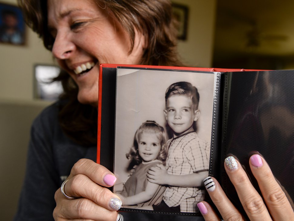 11Leah Hogsten | The Salt Lake Tribune Lisa Akers, 54, poses with a picture of her brother David and herself at the age of three-years-old at her home in Grantsville, May 11, 2019. Akers used DNA testing through 23andMe that led her to discover her birth mother and three half-sisters in February 2019. Akers and her family will get to meet her mother Lenore and half-sisters, Lenore, Karen and Kelly for the first time in Las Vegas on Wednesday and when she does, she will give her mother the photo album of herself when she was little.