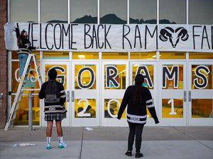 (Trent Nelson | The Salt Lake Tribune) Jane Erickson hangs a welcome back banner with help from Lavell and Olivia Manavahe as students return to Highland High School in Salt Lake City on Monday, Feb. 8, 2021. Starting next fall, the start time for the high school will be pushed back an hour to let students sleep in longer.