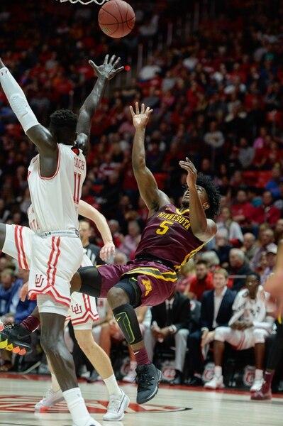 (Francisco Kjolseth | The Salt Lake Tribune) Minnesota Golden Gophers guard Marcus Carr (5) manages a shot on basket past Utah as Utah hosts Minnesota in NCAA basketball at the Huntsman Center in Salt Lake City on Friday, Nov. 15, 2019.