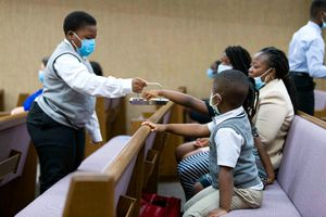 (The Church of Jesus Christ of Latter-day Saints) A young priesthood holder offers the sacrament to a family during a modified church service in the Carrollton Ward, Washington, D.C., Aug. 16, 2020. Due to the rise of the delta variant, some Latter-day Saint congregations are again requiring masks for in-person participants.