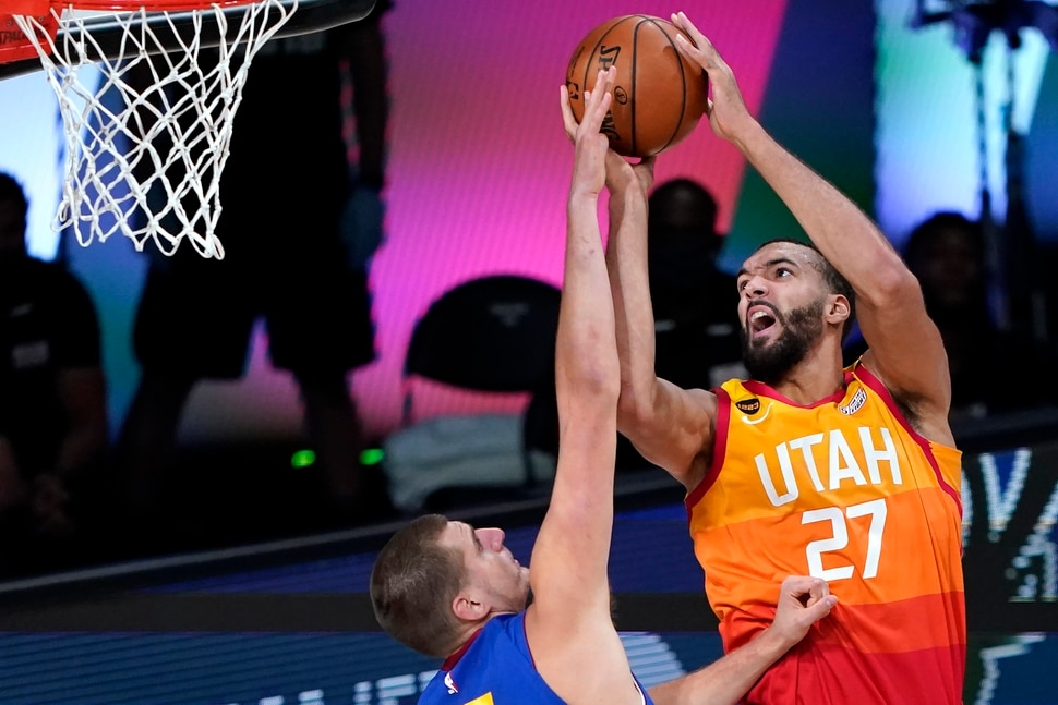 Utah Jazz's Rudy Gobert (27) goes up for a shot as Denver Nuggets' Nikola Jokic defends during the first half of an NBA basketball first round playoff game Sunday, Aug. 30, 2020, in Lake Buena Vista, Fla. (AP Photo/Ashley Landis)