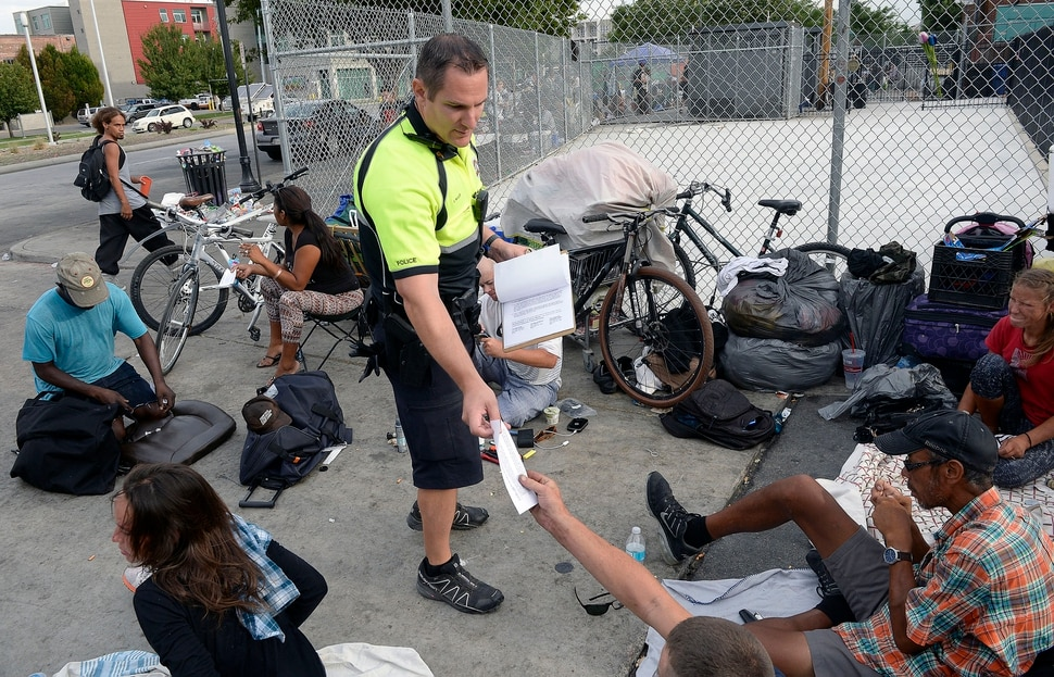 Al Hartmann | The Salt Lake Tribune Salt Lake City police officer Sgt. Sam Wolf talks to people near 200 S. and 500 W. Wednesday morning July 19 and gives them a note stating the city ordinance prohibiting camping on the street. He politely wakes up dozens of homeless camped on the sidewalks, telling them that they have to break down their camps and offers advice for help and rescources. Camping on the street is a class B misdemeanor and can now be enforced.
