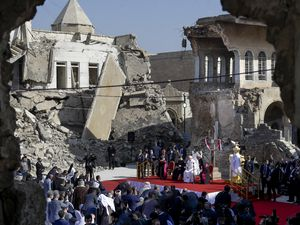 (Andrew Medichini | The Associated Press) Pope Francis, surrounded by shells of destroyed churches, leads a prayer for the victims of war at Hosh al-Bieaa Church Square, in Mosul, Iraq, once the de-facto capital of IS, Sunday, March 7, 2021. The long 2014-2017 war to drive IS out left ransacked homes and charred or pulverized buildings around the north of Iraq, all sites Francis visited on Sunday.