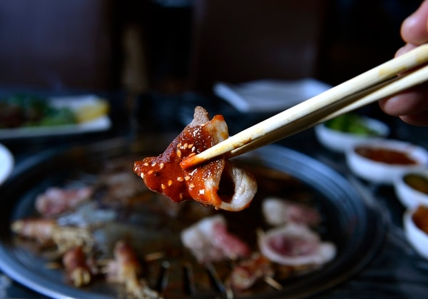 (Scott Sommerdorf | The Salt Lake Tribune) Pork belly dipped in a spicy sauce at Ombu Grill.