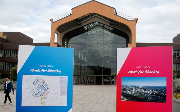 FILE - In this Monday May 15, 2017 file photo, a woman walks past the future Olympic Village for the Paris 2024 Olympic Games bid, in Saint-Denis, outside Paris. Los Angeles and Paris should edge closer Friday, June 9, 2017 to both getting Olympic host city rights later this year. Ahead of a key meeting of the International Olympic Committee executive board, the French capital is now seen as favorite to host the 2024 Summer Games. The strangest Olympic bidding race in four decades will take clearer shape when the IOC board weighs opening up the 2024 contest also to include the 2028 award in September. (AP Photo/Michel Euler, file)