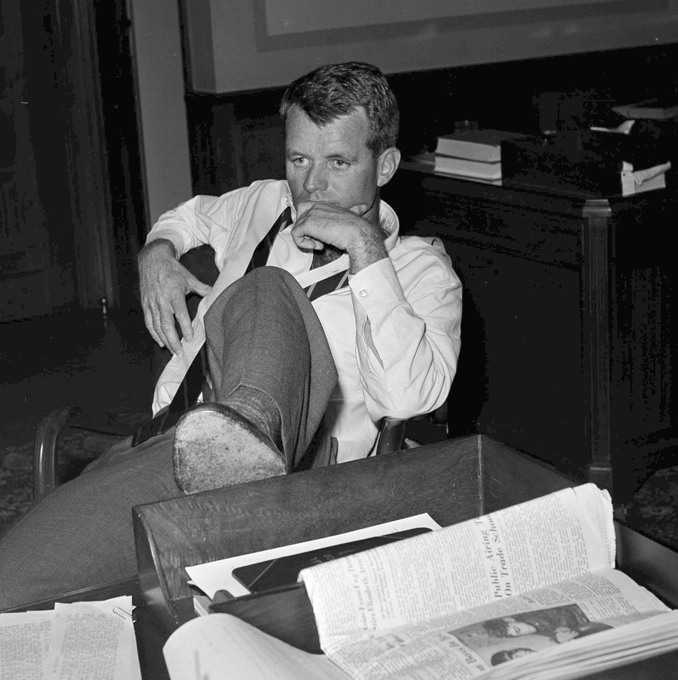 FILE - In this May 21, 1961, file photo, U.S. Attorney General Robert F. Kennedy, brother of President John F. Kennedy, rests his foot on a desk at the Justice Department, in Washington, D.C., while working with aides considering legal measures to be taken following racial violence, in Montgomery, Ala. Nearly 50 years after Kennedy's assassination, a new documentary series on his life and transformation into a liberal hero has come to Netflix.