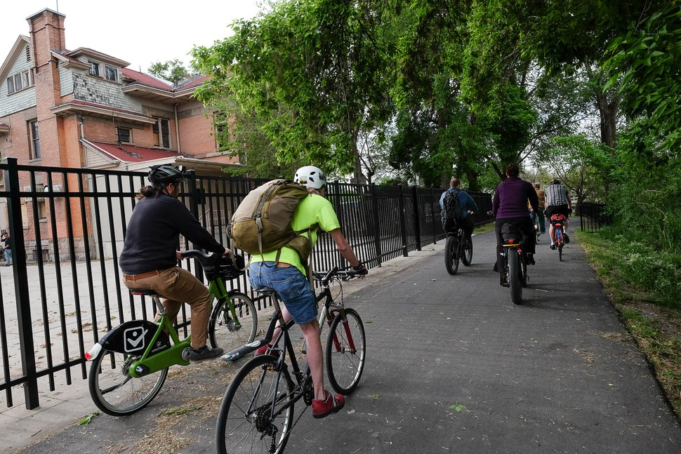 (Francisco Kjolseth | The Salt Lake Tribune) Cyclists joining the mayor's Bike to Work Day ride past the old Fisher Mansion and carriage house, which are situated along the Jordan River Trail.