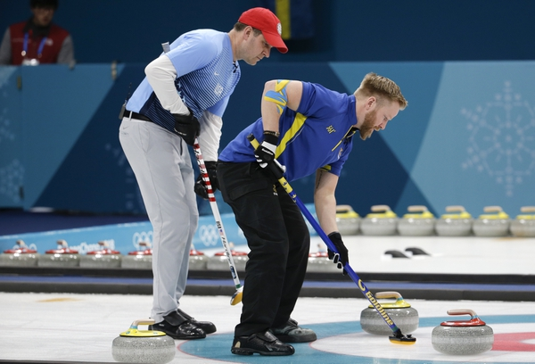 United States's skip John Shuster, left, and Sweden's skip Niklas Edin, sweep the ice during the men's final curling match at the 2018 Winter Olympics in Gangneung, South Korea, Saturday, Feb. 24, 2018. (AP Photo/Natacha Pisarenko)