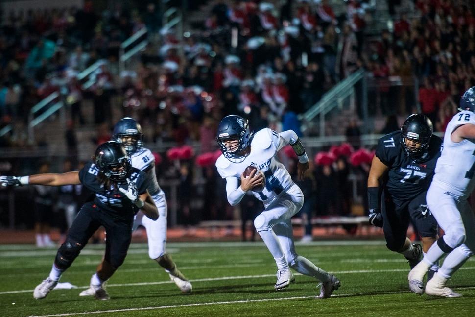 (Chris Detrick | The Salt Lake Tribune) Corner Canyon's Cole Hagen (14) runs past Alta's Brandon Folau (25) and Alta's Singi Pututau (77) during the game at Alta High School Thursday, October 12, 2017.