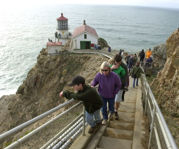 Visitors make their way up the steps leading to a lighthouse at the Point Reyes National Seashore in Point Reyes, Calif., Sunday, Dec. 29, 2002. The lighthouse was built in 1870 to keep sailors from crashing into the rocky shore as they navigated into and out of San Francisco Bay, 35 miles to the southeast. Today, an automated electric light and fog horn warn mariners of the rocky shore below, but the original Point Reyes Lighthouse, on the tip of a peninsula north of San Francisco, remains as a testament to California's maritime past. Years of wind, fog and harsh sea air have left the structure in need of repairs, so the 132-year-old lighthouse is being restored as part of a $1.2 million project by the National Park Service. (AP Photo/Marcio Jose Sanchez)