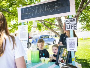 (Isaac Hale | Special to The Tribune) Makayla Madsen, 7, right, and her sister Myleigh, 9, fill customers' orders as the Madsen family works a lemonade stand in front of their home in West Jordan on Saturday, June 12, 2021. All proceeds from the lemonade stand were to be donated to DonorConnect in honor of the family's late daughter, Makenzie, who passed away last summer at the age of 14 while waiting for a heart transplant.