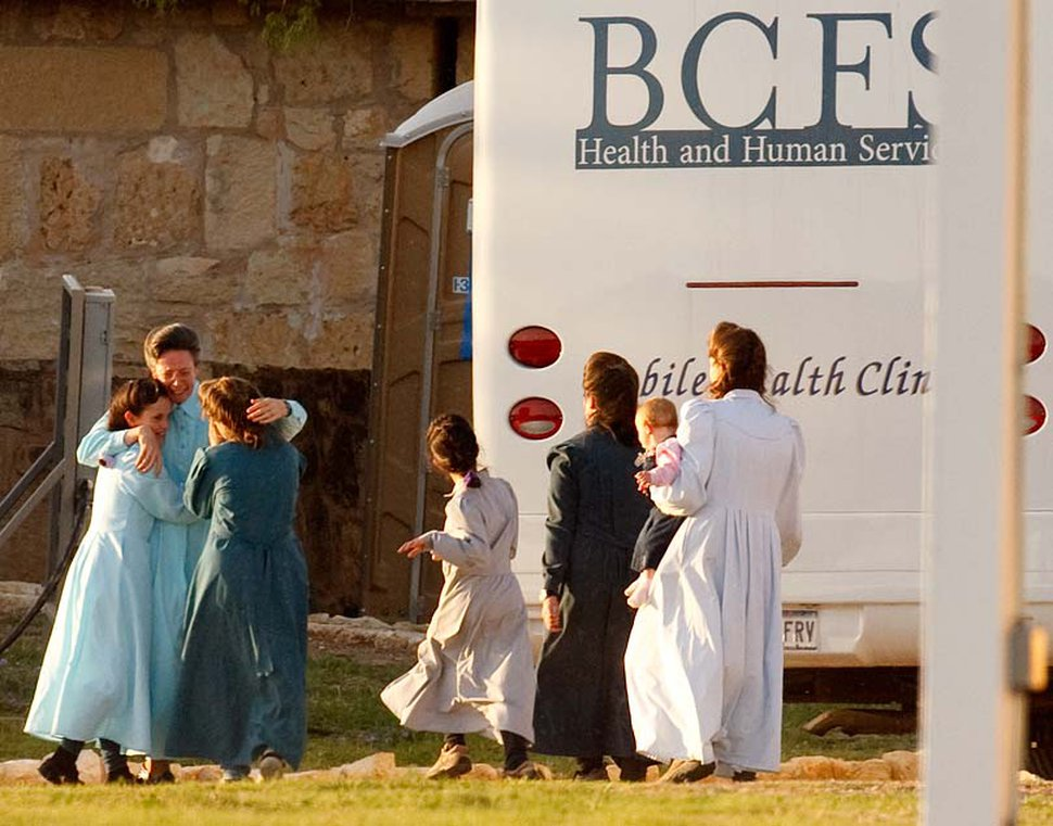 (Trent Nelson   The Salt Lake Tribune) San Angelo, Texas - Janet, an FLDS matriarch, tearfully embraces young girls as they arrive at the old historic Fort Concho, where nearly 500 FLDS women and children would be temporarily sheltered in primitive buildings such as former horse barns. The large amount of people that Texas Child Protective Services called victims overwhelmed the state's foster care system.