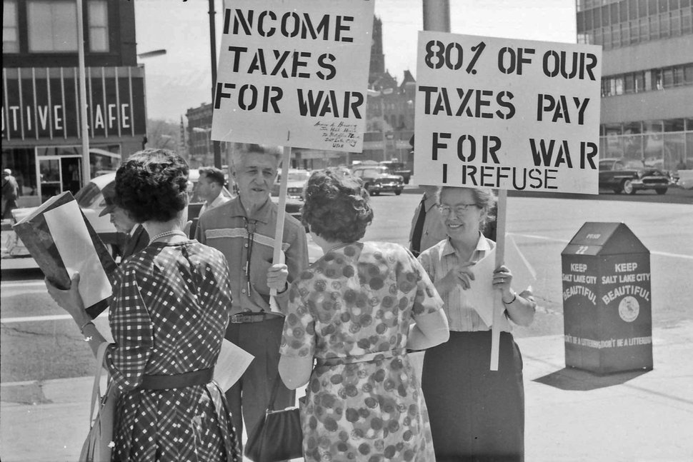 (photo courtesy Jerry Currier) Ammon Hennacy and Carol Gorgen speak to passersby at the corner of 400 S Main in downtown Salt Lake City as they protest paying taxes in 1961 because as pacifists they were opposed to funding the military.