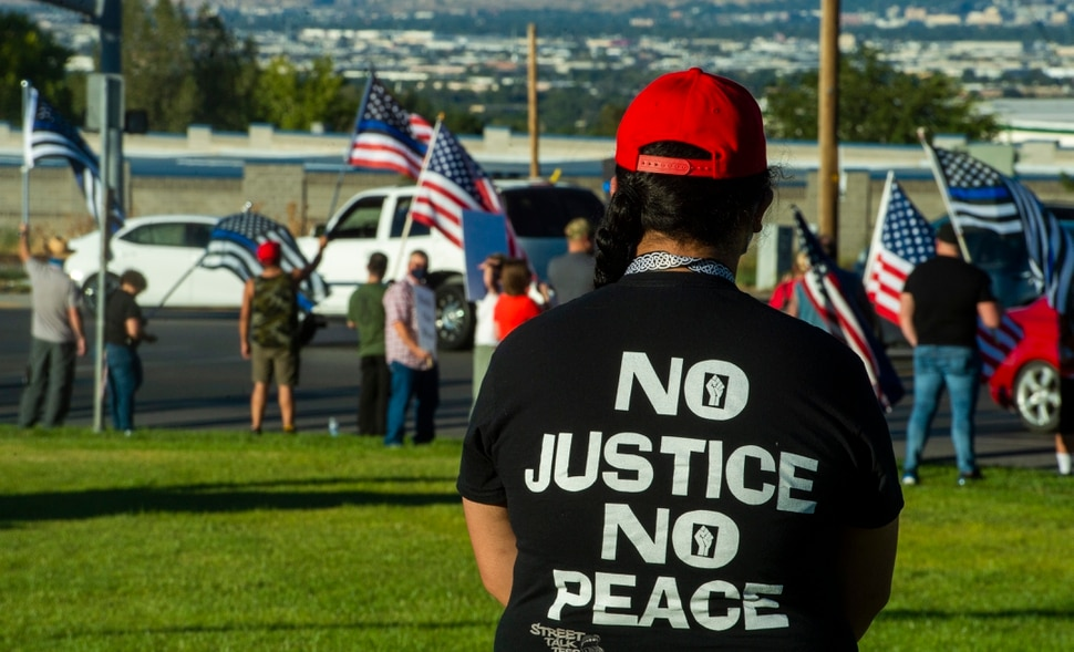 (Rick Egan | The Salt Lake Tribune) Tilesa Fotu watch from a distance as police supporters upset by a Pay Bagley cartoon wave flags, as they protest The Salt Lake Tribune in West Valley City, on Thursday, Sept. 3, 2020.