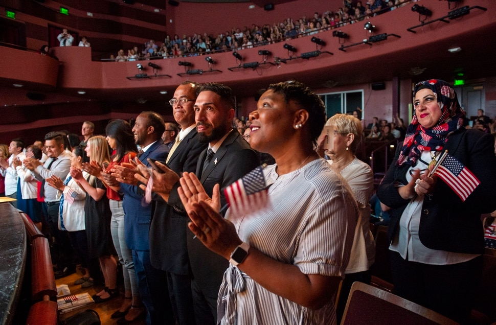 (Rick Egan | The Salt Lake Tribune) One hundred and twenty six new citizens of the United States clap as after taking the oath of citizenship, during a naturalization ceremony at the Jeanné Rose Wagner Theatre in Salt Lake City, Wednesday, July 3, 2019.