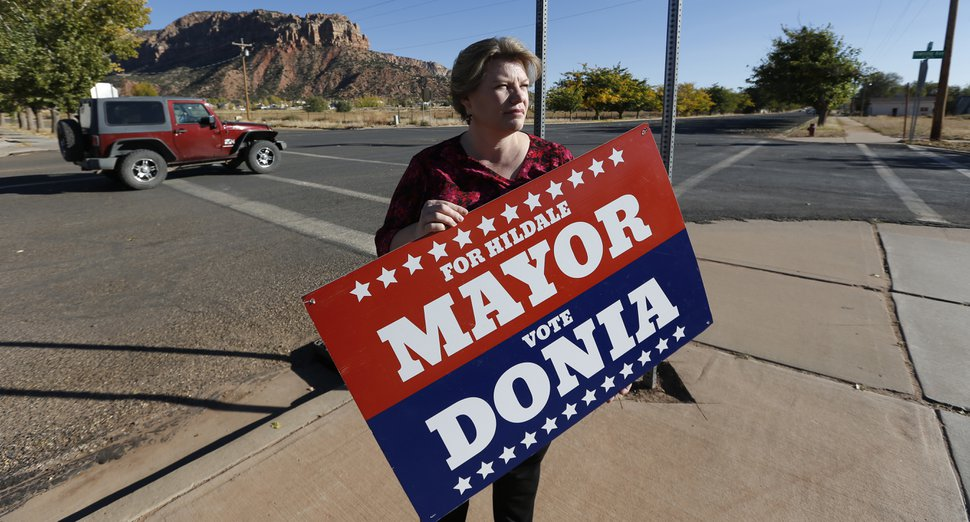 (Rick Bowmer | AP file photo) In this 2017 photo, Donia Jessop holds her mayoral campaign sign outside her store in Colorado City, Ariz. Campaign signs are unusual in a town where elections have long been quietly decided behind the scenes, with hand-picked men from the Fundamentalist Church of Jesus Christ of Latter-Day Saints running unopposed.
