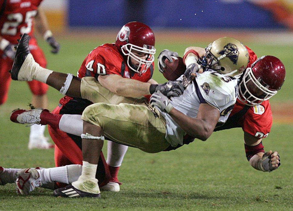 (AP Photo/Matt York) Pittsburgh's Tim Murphy is taken down by Utah's Tommy Hackenbruck (40) and Corey Dodds, right, in the second quarter at the Fiesta Bowl, Saturday, Jan. 1, 2005, in Tempe, Ariz.