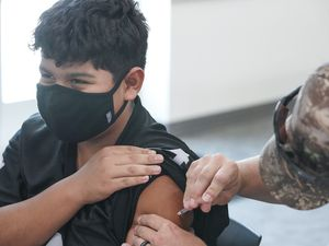(Leah Hogsten   The Salt Lake Tribune) Irvin Torres, 12, gets his Covid vaccine from MSgt. Colton Shakespear with the Army National Guard. Torres just turned 12 in July and was receiving his second shot in August. The Pfizer-BioNTech coronavirus vaccine has been shown to be safe and highly effective in young children ages 5 to 11 years, the companies announced early Monday morning.
