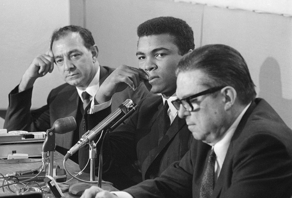 FILE - In this Jan. 11, 1967, file photo, heavyweight champion Muhammad Ali ponders a question during his news conference after his arrival in Houston. Ali, who was 1-A after he lost his bid to be classified as a conscientious objector, had been notified of the decision before the news conference. He is scheduled to take on Ernie Terrell Feb. 6 to clear up the heavyweight title difference. At right is Judge Roy Hofheinz. Man at left is unidentified. (AP Photo/Ed Kolenovsky, File)