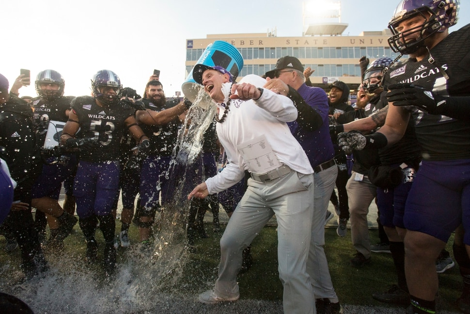 Weber State coach Jay Hill is doused by players after Weber State defeated Idaho State 35-7 in an NCAA college football game, to win a share of the Big Sky Conference championship Saturday, Nov. 18, 2017, in Ogden, Utah. (Matt Herp/Standard-Examiner via AP)