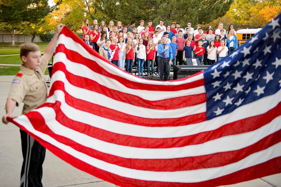 (Trent Nelson | The Salt Lake Tribune) Students in the South Jordan Middle School Concert Choir look on as boy scouts raise the flag at sunrise to mark the anniversary of 9/11, Tuesday Sept. 11, 2018.