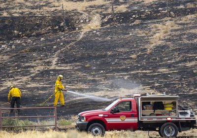 (Rick Egan   The Salt Lake Tribune) Firefighters spray hot spots on a wildfire fire in Herriman on Friday, July 16, 2021. Rep. Blake Moore, R-Utah, is pushing a federal bill to help in the battle against wildfires.