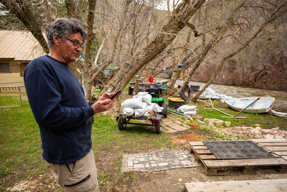 (Trent Nelson | The Salt Lake Tribune) Wayne Hill checks water level reports on his phone while anticipating possible flooding at his home on the banks of the South Fork Ogden River east of Huntsville on Monday April 22, 2019.
