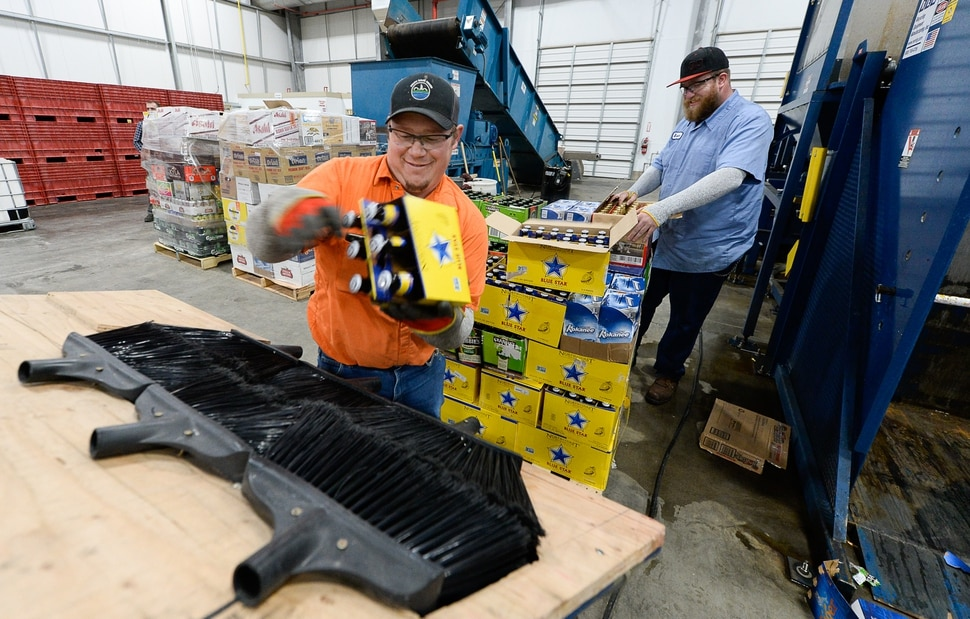 (Francisco Kjolseth | The Salt Lake Tribune) Operators Jayson Dlugas, left, and Braeden Adamson drop beer bottles into a glass recycler as the DABC delivers 275 cases of beer on three pallets to the new food digester in North Salt Lake on Friday, Dec. 13, 2019. The state can no longer sell the beer — all between 4% and 5% ABV — because it can't compete with privately owned grocery and convenience stores which started selling the higher alcohol brews on Nov. 1.