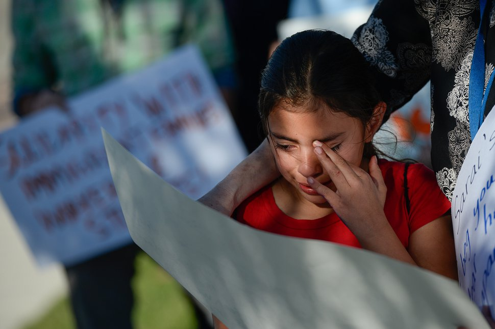 (Francisco Kjolseth | The Salt Lake Tribune) Sarai Reyes, 9, cries as she speaks with the help of her 4th grade teacher while surrounded by community members who gathered in front of Immigration and Customs Enforcement offices in West Valley City on Monday, Oct. 16, 2017, to support Maria Santiago Garcia, a single Utah mother of four U.S. born children who faces an impending deportation order.