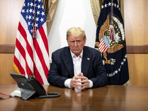 (Tia Dufour | The White House via AP) In this image provided by the White House, President Donald Trump in his conference room at Walter Reed National Military Medical Center in Bethesda, Md., Sunday, Oct. 4, 2020.