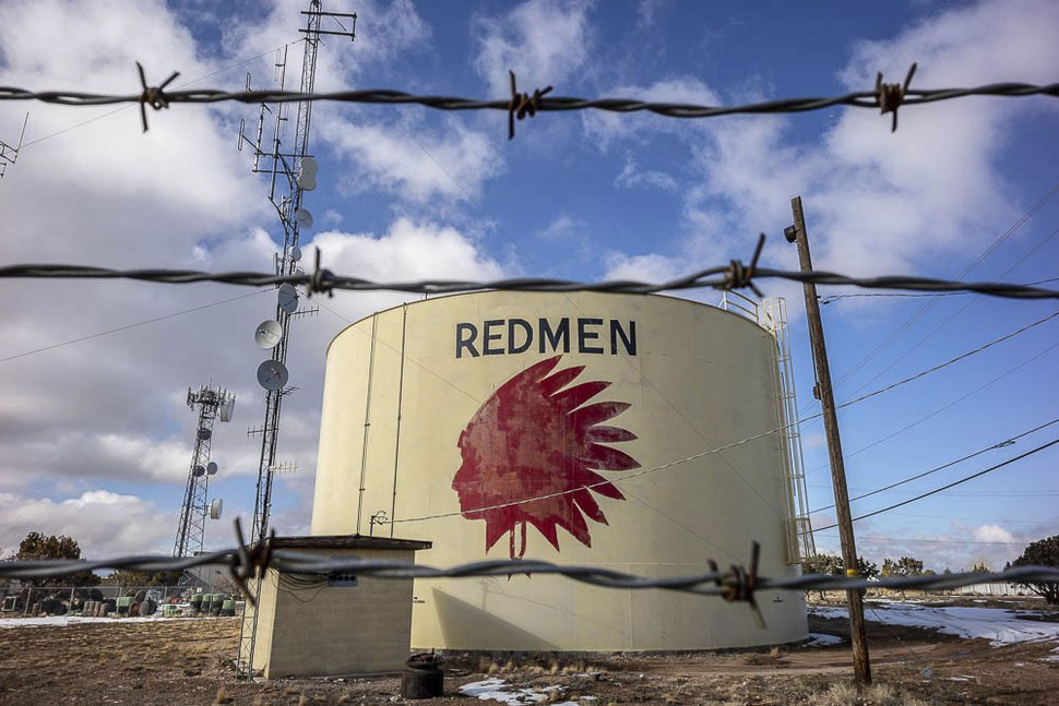 In this Friday Jan. 11, 2019 photo, a water tank sits above Cedar City, Utah, with the Redmen mascot of Cedar High School displayed on it. The painted image of a Native American and the name
