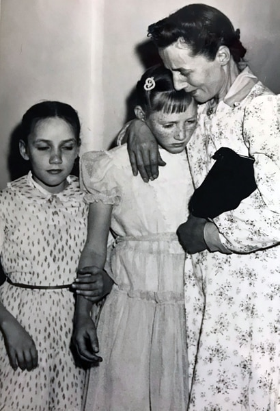(Tribune file photo) Vera Johnson Black comforts Elsie, 11, as Emily, 9, holds her sister's arm. Black's children were placed in state custody after the 1953 raid on Short Creek, which lead to a Utah Supreme Court case.