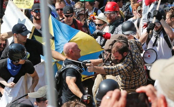 White nationalist demonstrators clash with counter demonstrators at the entrance to Lee Park in Charlottesville, Va., Saturday, Aug. 12, 2017. Gov. Terry McAuliffe declared a state of emergency and police dressed in riot gear ordered people to disperse after chaotic violent clashes between white nationalists and counter protestors. (AP Photo/Steve Helber)