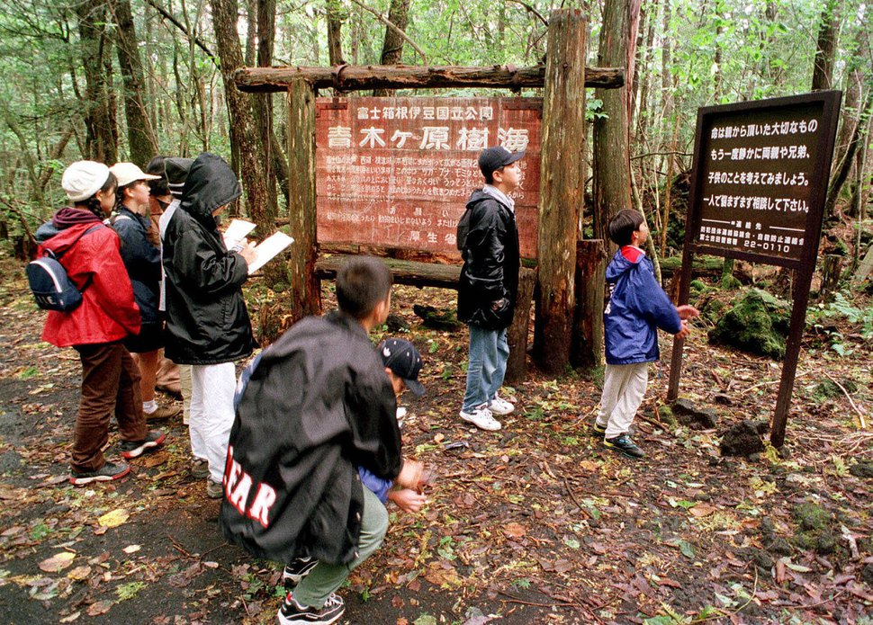 FILE - in this Thursday, Oct. 22, 1998, file photo a group of schoolchildren read signs posted in the dense woods of the Aokigahara Forest at the base of Mount Fuji, Japan.YouTube says it has removed blogger Logan Paul's channels from Google Preferred and will not feature him in the new season of