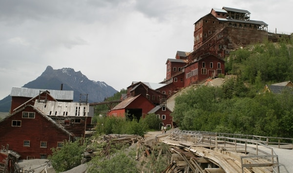 A wooden footbridge over National Creek, lower right, which provided access to the historic red buildings of the Kennecott Mine near McCarthy, Alaska, is shown in this June 2005 photo. Early October 2006 floodwaters knocked out tripod supports of the decades-old trestle to the bridge, leaving no safe way into or out of the historic site. Park officials aren't sure how, or if, they're going to fix flood damage to one of the state's popular destinations for both Alaskans and tourists. (AP Photo/Andrew Krueger)