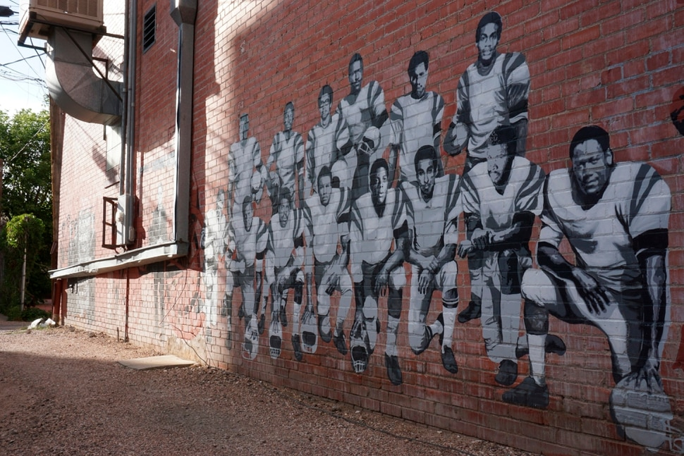 (Mead Gruver | AP Photo) In this Wednesday, Sept. 11, 2019 photo shows part of an alleyway mural in downtown Laramie, Wyo., that honors the Black 14. The Black 14 were black athletes dismissed from the University of Wyoming football team in 1969 for seeking to protest racism by wearing black armbands in a game against Brigham Young University. The university plans to dedicate a plaque honoring the group at War Memorial Stadium on Friday.
