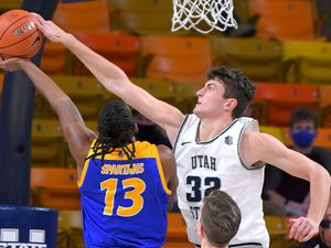 San Jose State guard Seneca Knight (13) has his shot blocked by Utah State center Trevin Dorius (32) as forward Justin Bean (34) helps defends during the first half of an NCAA college basketball game Wednesday, Dec. 23, 2020, in Logan, Utah. (Eli Lucero/The Herald Journal via AP, Pool)