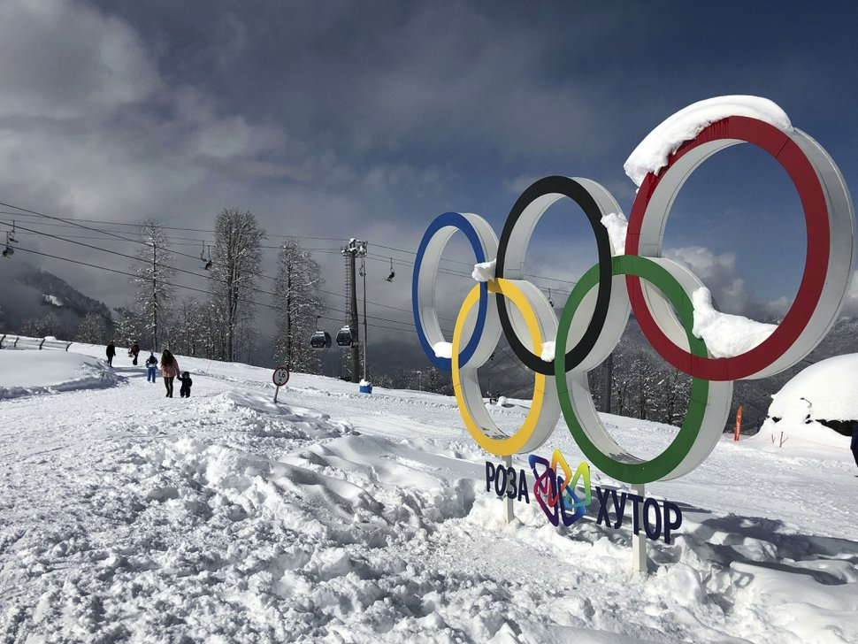 (AP File Photo/James Ellingworth) Tourists walk next to the Olympic rings on the mountain resort of Krasnaya Polyana near the Black Sea resort of Sochi, southern Russia, on March 3, 2019. In the five years since the Sochi Olympics, Russians have been flocking south to enjoy their subtropical ski slopes.